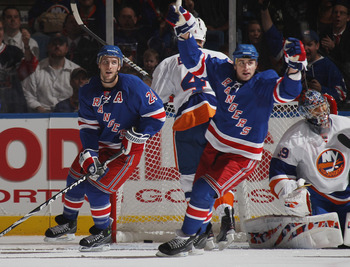 UNIONDALE, NY - OCTOBER 11: (L-R) Brandon Dubinsky #24 and Ryan Callahan #17 of the New York Rangers celebrate a power play goal by Michael Del Zotto (not shown) at 8:28 of the second period against the New York Islanders at the Nassau Coliseum on October