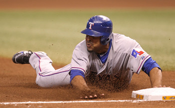 ST. PETERSBURG, FL - OCTOBER 12:  Nelson Cruz #17 of the Texas Rangers slides into third forcing a throwing error on catcher Kelly Shoppach during Game 5 of the ALDS at Tropicana Field on October 12, 2010 in St. Petersburg, Florida.  (Photo by Mike Ehrman