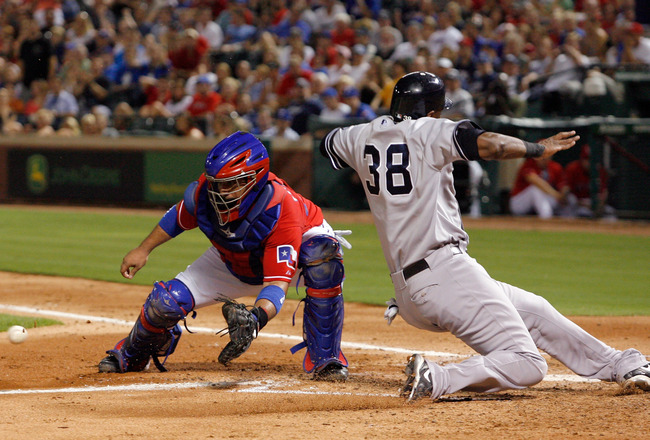 ARLINGTON, TX - SEPTEMBER 10:  Designated hitter Marcus Thames #38 of the New York Yankees slides into home plate to score against catcher Bengie Molina #11 of the Texas Rangers on September 10, 2010 at Rangers Ballpark in Arlington, Texas.  (Photo by Tom