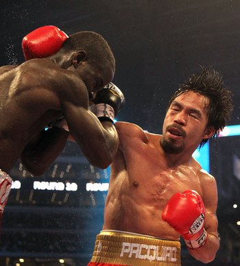 ARLINGTON, TX - MARCH 13:  (R-L) Manny Pacquiao of the Philippines throws a right to the head of Joshua Clottey of Ghana during the WBO welterweight title fight at Cowboys Stadium on March 13, 2010 in Arlington, Texas. Pacquiao defeated Clottey by unanimo
