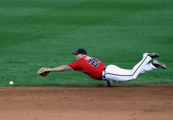 ATLANTA - OCTOBER 10:  Brooks Conrad #26 of the Atlanta Braves dives for a ball during Game Three of the NLDS of the 2010 MLB Playoffs against the San Francisco Giants on October 10, 2010 at Turner Field in Atlanta, Georgia.  (Photo by Jamie Squire/Getty