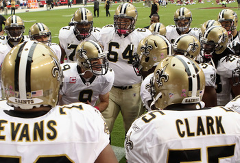 GLENDALE, AZ - OCTOBER 10:  Quarterback Drew Brees #9 of the New Orleans Saints talks with teammates in a huddle prior to the NFL game against the Arizona Cardinals at the University of Phoenix Stadium on October 10, 2010 in Glendale, Arizona. The Cardina