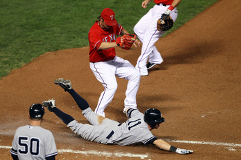 ARLINGTON, TX - OCTOBER 15:  Brett Gardner #11 of the New York Yankees slides into first safely ahead of the tag of pitcher C.J. Wilson #36 of the Texas Rangers in Game One of the ALCS during the 2010 MLB Playoffs at Rangers Ballpark in Arlington on Octob