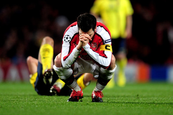 LONDON, ENGLAND - MARCH 31:  Cesc Fabregas of Arsenal reacts after being shown a yellow card by referee Massimo Busacca of Switerland during the UEFA Champions League quarter final first leg match between Arsenal and FC Barcelona at the Emirates Stadium o