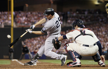 MINNEAPOLIS - OCTOBER 07:  Mark Teixeira #25 of the New York Yankees gets a hit as Joe Mauer #7 of the Minnesota Twins catches during game two of the ALDS on October 7, 2010 at Target Field in Minneapolis, Minnesota.  (Photo by Elsa/Getty Images)