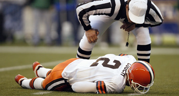 SEATTLE - NOVEMBER 30:  Referee Ed Hochuli #85 looks to help Quarterback Tim Couch #2 of the Cleveland Browns as he lays hurt during the game against the Seattle Seahawks on November 30 2003 at Seahawks Stadium in Seattle, Washington. The Seahawks defeate
