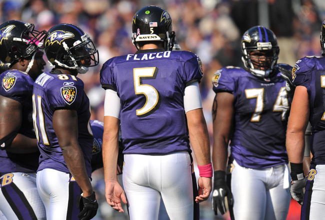 BALTIMORE, MD - OCTOBER 10: Joe Flacco #5 of the Baltimore Ravens huddles the offense during the game against the Denver Broncos at M&T Bank Stadium on October 10, 2010 in Baltimore, Maryland. Players wore pink in recognition of Breast Cancer Awareness Mo