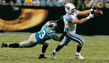 CHARLOTTE, NC - AUGUST 28: Wide receiver Damian Williams #17 of the Tennessee Titans drops the ball as Jamar Williams #53 of the Carolina Panthers drags him down during their preseason game at Bank of America Stadium on August 28, 2010 in Charlotte, North