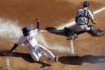 ARLINGTON, TX - OCTOBER 16:  Elvis Andrus #1 of the Texas Rangers slides into home plate to score on a double steal in the bottom of the first inning against Jorge Posada #20 of the New York Yankees in Game Two of the ALCS during the 2010 MLB Playoffs at