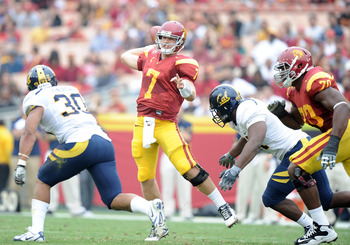 LOS ANGELES, CA - OCTOBER 16:  Matt Barkley #7 of the USC Trojans scrambles to make a pass in front of Mychal Kendricks #30 and Cameron Jordan #97 of the California Golden Bears during the first quarter at Los Angeles Memorial Coliseum on October 16, 2010