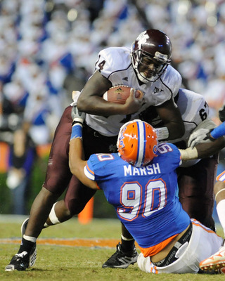 GAINESVILLE, FL - OCTOBER 16:  Quarterback Chris Relf #14 of the Mississippi State Bulldogs runs upfield against nose tackle Lawrence March #90 of the Florida Gators  October 16, 2010 Ben Hill Griffin Stadium at Gainesville, Florida.  (Photo by Al Messers