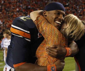 AUBURN - OCTOBER 16:  Quarterback Cam Newton #2 of the Auburn Tigers hugs a fan after the game against the Arkansas Razorbacks at Jordan-Hare Stadium on October 16, 2010 in Auburn, Alabama.  The Tigers beat the Razorbacks 65-43.  (Photo by Mike Zarrilli/G