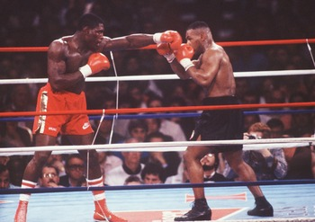 25 FEB 1989:  HEAVYWEIGHT CHAMPION MIKE TYSON BLOCKS AS CHALLENGER FRANK BRUNO  OF GREAT BRITAIN THROWS A RIGHT AT HIM DURING THEIR HEAVYWEIGHT TITLE FIGHT AT THE HILTON IN LAS VEGAS. TYSON STOPPED BRUNO IN THE FIFTH ROUND WITH A KNOCK OUT TO RETAIN HISTI