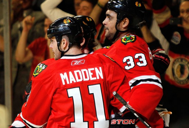 CHICAGO - JANUARY 14: John Madden #11 and Kris Versteeg #32 of the Chicago Blackhawks celebrate with teammate Dustin Byfuglien #33 after Byfuglien's second period goal against the Columbus Blue Jackets at the United Center on January 14, 2010 in Chicago,