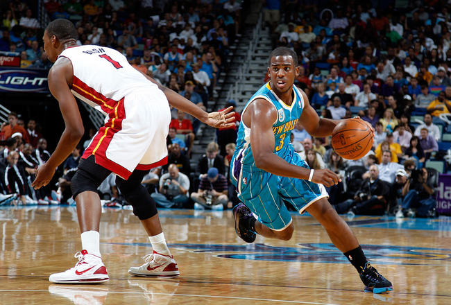 NEW ORLEANS - OCTOBER 13:  Chris Paul #3 of the New Orleans Hornets drives the ball around Chris Bosh #1 of the Miami Heat at the New Orleans Arena on October 13, 2010 in New Orleans, Louisiana. NOTE TO USER: User expressly acknowledges and agrees that, b