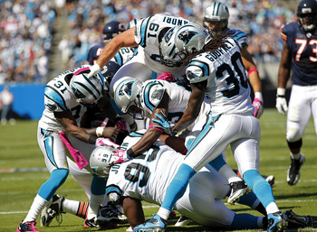 CHARLOTTE, NC - OCTOBER 10: Defensive tackle Ed Johnson #99 of the Carolina Panthers is mobbed by teammates after an interception against the Chicago Bears at Bank of America Stadium on October 10, 2010 in Charlotte, North Carolina. (Photo by Geoff Burke/