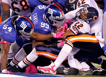 EAST RUTHERFORD, NJ - OCTOBER 03:  Matt Forte #22 of the Chicago Bears is tackled by Jonathan Goff #54 and Chris Canty #99 of the New York Giants at New Meadowlands Stadium on October 3, 2010 in East Rutherford, New Jersey.  (Photo by Michael Heiman/Getty