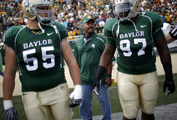WACO, TX - NOVEMBER 14:  Sgt. Mark Todd of the Fort Hood Police Department walks onto the field with center J.D. Walton #55 and nose tackle Trey Bryant #97 of the Baylor Bears to conduct the coin toss prior to the Texas Longhorns taking on the Baylor Bear
