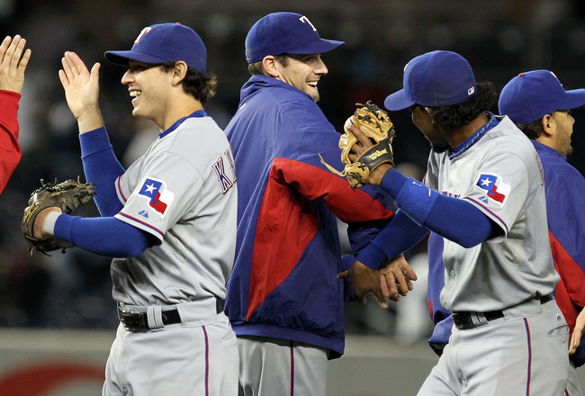 NEW YORK - OCTOBER 18:  (L-R) Ian Kinsler #5, Cliff Lee #33 and Elvis Andrus #1 of the Texas Rangers celebrate after the Rangers won 8-0 against the New York Yankees in Game Three of the ALCS during the 2010 MLB Playoffs at Yankee Stadium on October 18, 2
