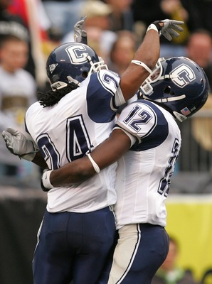 CHARLOTTE, NC - DECEMBER 29:  Teammates Larry Taylor #24 and Marcus Easley #12 of the Connecticut Huskies celebrate after Taylors touchdown against the Wake Forest Demon Deacons at Bank of America Stadium on December 29, 2007 in Charlotte, North Carolina.