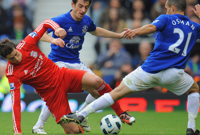 LIVERPOOL, ENGLAND - OCTOBER 17: Fernando Torres of Liverpool is tackled by Leighton Baines and Leon Osman of Everton during the Barclays Premier League match between Everton and Liverpool at Goodison Park on October 17, 2010 in Liverpool, England.  (Phot