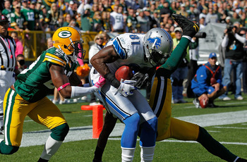 GREEN BAY, WI - OCTOBER 03: Calvin Johnson #81 of the Detroit Lions drops to the end zone after catching a touchdown pass between Derrick Martin #29 and Charles Woodson #21 of the Green Bay Packers at Lambeau Field on October 3, 2010 in Green Bay, Wiscons