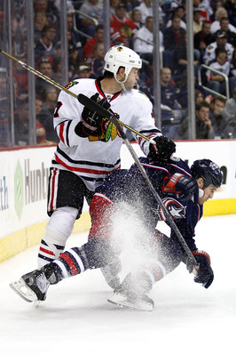 COLUMBUS,OH - October 15:   Brent Seabrook #7 of the Chicago Blackhawks checks Chris Clark #11 of the Columbus Blue Jackets while chasing down a loose puck during the second period on October 15, 2010 at Nationwide Arena in Columbus, Ohio.  (Photo by John