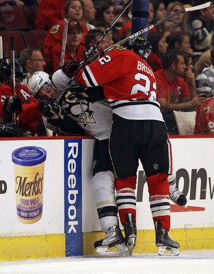 CHICAGO - OCTOBER 01: Troy Brouwer #22 of the Chicago Blackhawks checks Simon Despres #47 of the Pittsburgh Penguins into the Blackhawk bench during a pre-season game at the United Center on October 1, 2010 in Chicago, Illinois. (Photo by Jonathan Daniel/