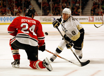CHICAGO - OCTOBER 01: Pascal Dupuis #9 of the Pittsburgh Penguins and Nick Boynton #24 of the Chicago Blackhawks battle for the puck during a pre-season game at the United Center on October 1, 2010 in Chicago, Illinois. The Blackhawks defeated the Penguin