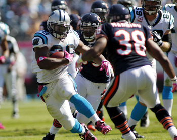 CHARLOTTE, NC - OCTOBER 10: Running back Jonathan Stewart #28 of the Carolina Panthers runs with the ball as defensive end Julius Peppers #90 and safety Danieal Manning #38 of the Chicago Bears defend at Bank of America Stadium on October 10, 2010 in Char