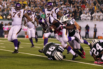 EAST RUTHERFORD, NJ - OCTOBER 11:  Adrian Peterson #28 of the Minnesota Vikings runs the ball against Sione Pouha #91 and David Harris #52 of the New York Jets at New Meadowlands Stadium on October 11, 2010 in East Rutherford, New Jersey. The Jets won 29-