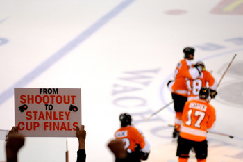 PHILADELPHIA - MAY 24:  A fan holds up a sign reading 'From Shootout to Stanley Cup Finals as the Philadelphia Flyers celebrate on the ice after an empty net goal in the third period against the Montreal Canadiens in Game 5 of the Eastern Conference Final