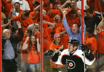 PHILADELPHIA - MAY 15:  Jeremy Roenick #97 of the Philadelphia Flyers celebrates a goal by Mark Recchi #8 against the Tampa Bay Lightning in Game four of the 2004 NHL Eastern Conference Finals on May 15, 2004 at the Wachovia Center in Philadelphia, Pennsy