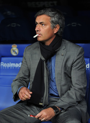MADRID, SPAIN - OCTOBER 19:  Head coach Jose Mourinho of Real Madrid eats a piece of chewing gum while seated on the bench prior to the start of the UEFA Champions League group G match between Real Madrid and AC Milan at the Estadio Santiago Bernabeu on O