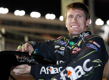 CONCORD, NC - OCTOBER 14:  Carl Edwards, driver of the #99 Aflac Ford, climbs out of his car after qualifying for the NASCAR Sprint Cup Series Bank of America 500 at Charlotte Motor Speedway on October 14, 2010 in Concord, North Carolina.  (Photo by Geoff