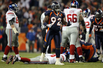 DENVER - NOVEMBER 26:  Elvis Dumervil #92 of the Denver Broncos reacts after forcing a fumble by quarterback Eli Manning #10 of the New York Giants leading to a Broncos recovery during NFL action at Invesco Field at Mile High on November 26, 2009 in Denve