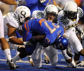 BOISE, ID - SEPTEMBER 3: Linebacker Spencer Paysinger #35, defensive lineman Brandon Bair #88 and safety Javes Lewis #14 of the Oregon Ducks gang up to tackle running back Jeremy Avery #27 of the Boise State Broncos in the second quarter of the game on Se
