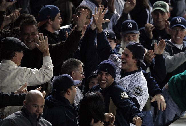 NEW YORK - OCTOBER 19:  A fan (R) of the New York Yankees reacts after he caught a home run ball hit by Robinson Cano #24 of the Yankees in the bottom of the seocnd inning against the Texas Rangers in Game Four of the ALCS during the 2010 MLB Playoffs at