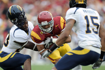 LOS ANGELES, CA - OCTOBER 16:  Robert Woods #13 of the USC Trojans is tackled by Josh Hill #23 and Bryant Nnabuife #15 of the California Golden Bears during the second quarter at Los Angeles Memorial Coliseum on October 16, 2010 in Los Angeles, California