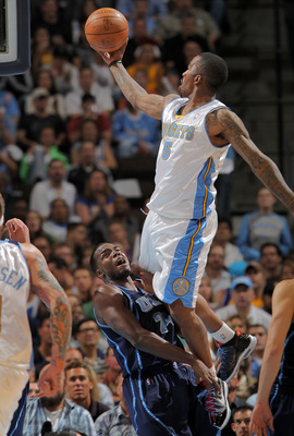 DENVER - APRIL 28:  J. R. Smith #5 of the Denver Nuggets is called for an offensive foul as he goes up for a shot over Paul Millsap #24 of the Utah Jazz in Game Five of the Western Conference Quarterfinals of the 2010 NBA Playoffs at the Pepsi Center on A