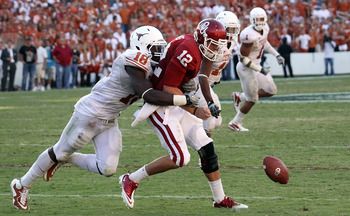 DALLAS - OCTOBER 02:  Quarterback Landry Jones #12 of the Oklahoma Sooners fumbles the ball against D.J. Grant #18 of the Texas Longhorns in the fourth quarter at the Cotton Bowl on October 2, 2010 in Dallas, Texas.  (Photo by Ronald Martinez/Getty Images