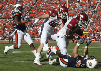 AUBURN - OCTOBER 16:  Fullback Van Stumon #44 of the Arkansas Razorbacks (second from right) runs over linebacker Jake Holland #5 of the Auburn Tigers (on the ground) while tight end Garrett Uekman #88 of the Arkansas Razorbacks (center) looks on during t