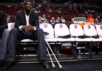 PORTLAND, OR - OCTOBER 10:  Greg Oden #52 of the Portland Trail Blazers, who is out for the season after under going micro fracture surgery in his knee, sits on the bench to watch a pre-season game against the Los Angeles Clippers at the Rose Garden on Oc