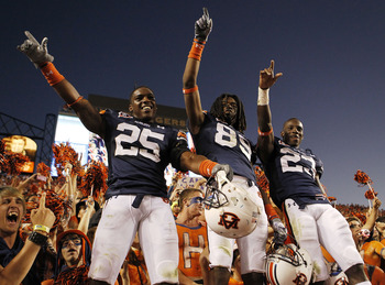 AUBURN - OCTOBER 16:  Linebacker Daren Bates #25, wide receiver Darvin Adams #89 and running back Onterio McCalebb #23 of the Auburn Tigers celebrate with the crowd after the game against the Arkansas Razorbacks at Jordan-Hare Stadium on October 16, 2010