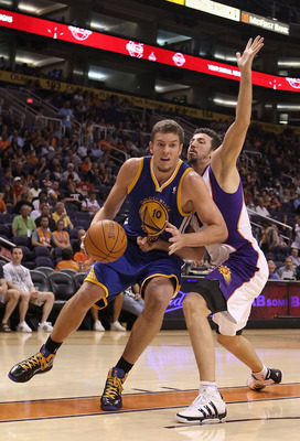PHOENIX - OCTOBER 19:  David Lee #10 of the Golden State Warriors handles the ball under pressure from Hedo Turkoglu #19 of the Phoenix Suns during the preseason NBA game at US Airways Center on October 19, 2010 in Phoenix, Arizona. NOTE TO USER: User exp