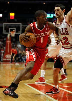 CHICAGO - MARCH 22: Aaron Brooks #0 of the Houston Rockets drives around Kirk Hinrich #12 of the Chicago Bulls at the United Center on March 22, 2010 in Chicago, Illinois. The Bulls defeated the Rockets 98-88. NOTE TO USER: User expressly acknowledges and