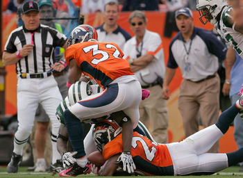 DENVER - OCTOBER 17:  Renaldo Hill #23 of the Denver Broncos recovers a fumble by Santonio Holmes #10 of the New York Jets in the third quarter at INVESCO Field at Mile High on October 17, 2010 in Denver, Colorado.  (Photo by Justin Edmonds/Getty Images)