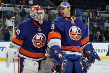 UNIONDALE, NY - OCTOBER 16:  Dwayne Roloson #30 and Rick DiPietro #39 of the New York Islanders celebrate after defeating the Colorado Avalanche on October 16, 2010 at Nassau Coliseum in Uniondale, New York. The Isles defeated the Avalanche 5-2.  (Photo b