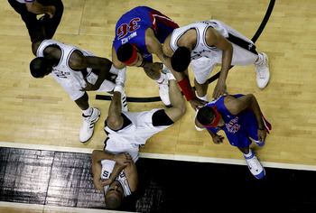 SAN ANTONIO - JUNE 21:  Tony Parker #9 of the San Antonio Spurs lays on the ground hurt as teammates Nazr Mohammed #2, Tim Duncan #21  and Rasheed Wallace #36 and Richard Hamilton #32 of the Detroit Pistons pause in the stoppage of play during the first h
