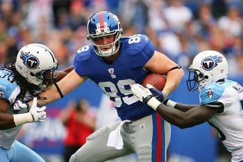 EAST RUTHERFORD, NJ - SEPTEMBER 26: Kevin Boss #89 of the New York Giants is tackeld by Michael Griffen #33 (L) and Jason McCourty #30 of the Tennessee Titans after completing a 54 yard reception in the first quarter at New Meadowlands Stadium on Septembe
